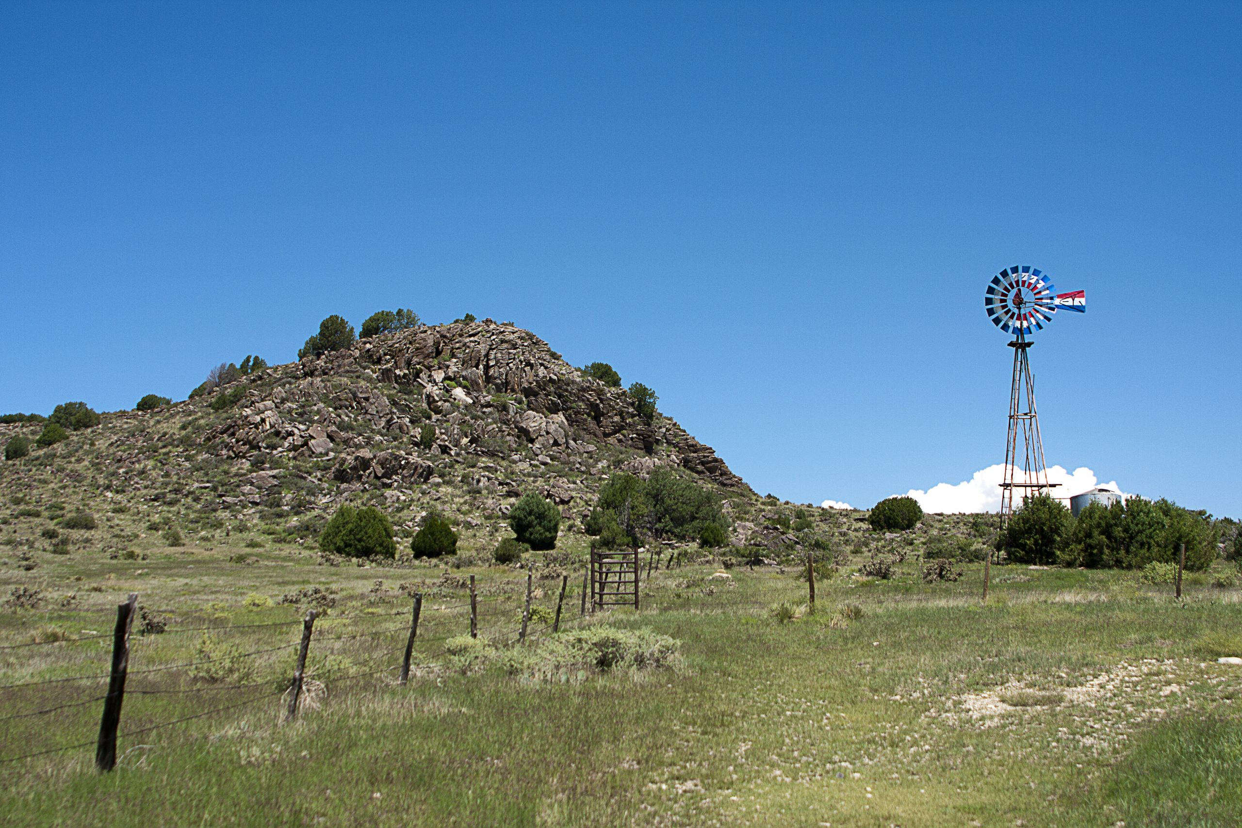 Rocky hill next to red, white, and blue windmill