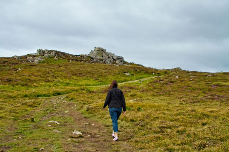 Woman hiking through a green field