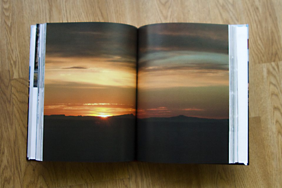 Photo book with a two-page spread of a sunset