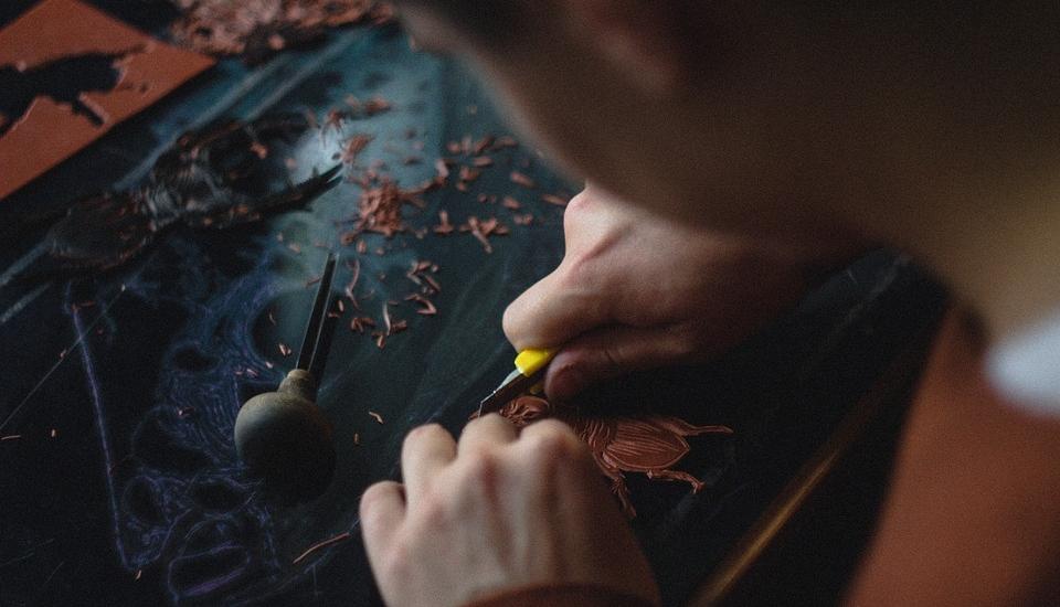 Linocut artist carving a block