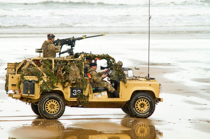 Soldiers in a military vehicle giving a demonstration on a beach
