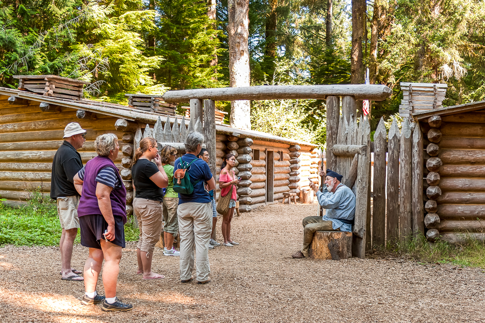 A crowd of visitors listen to a guide dressed in interpretive clothing at the gates of Fort Clatsop, a log fort in Oregon