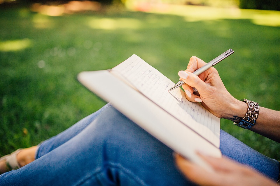 Woman sitting in the grass, writing in a journal