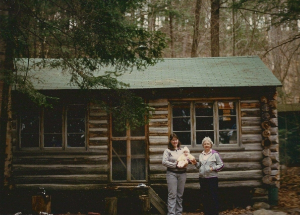 Two women and a baby in front of a rustic log cabin in the woods