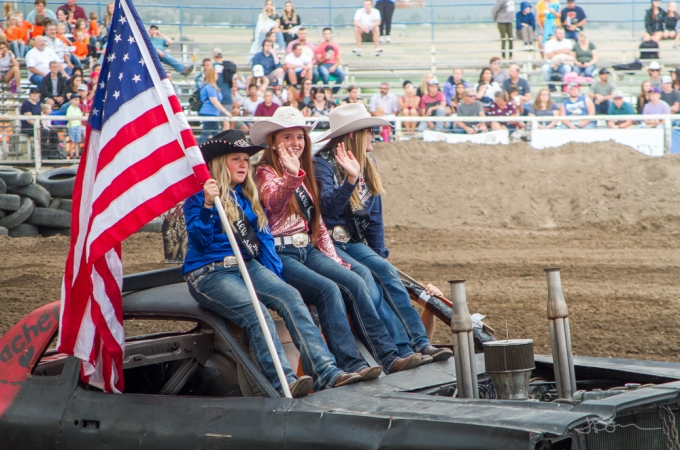 Rodeo queens riding into an arena on a demolition derby car, holding an American flag