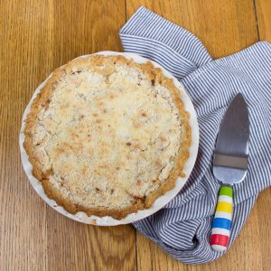 Apple pie and pie server on a blue and white towel