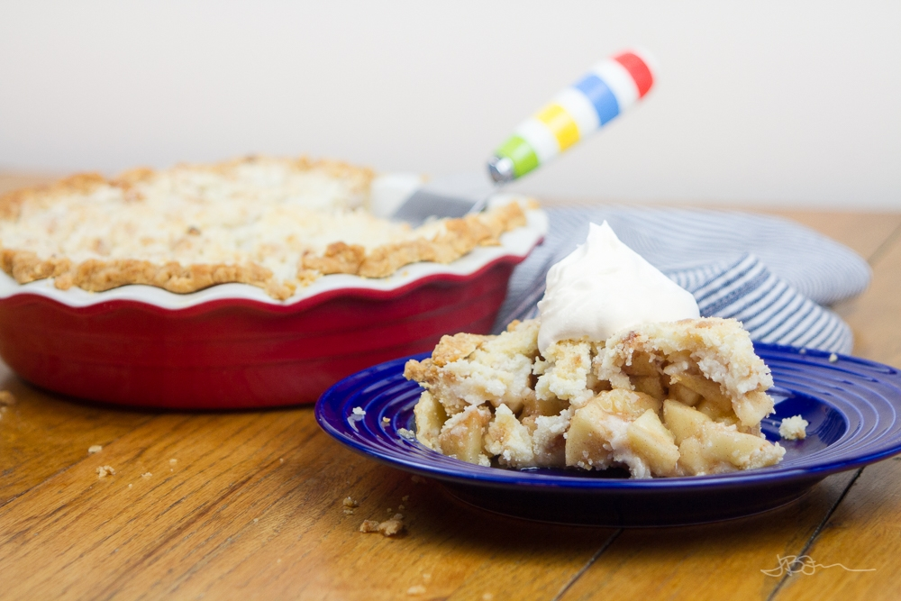 Slice of apple pie topped with whipped topping