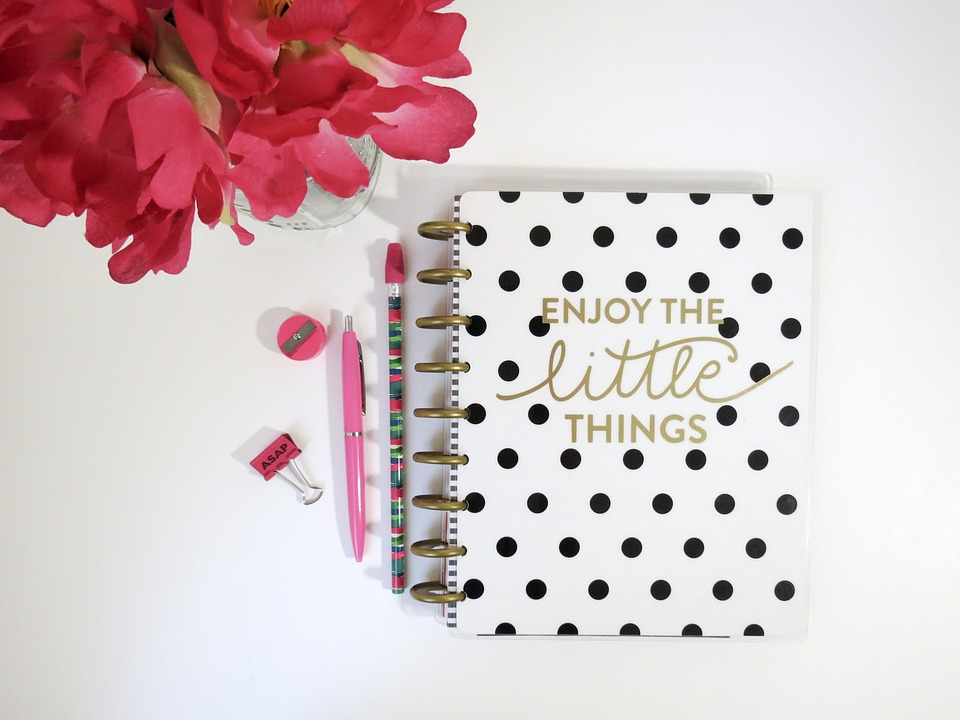 Black and white polka dotted journal next to some pink flowers and writing implements