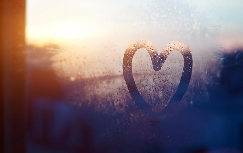 Heart drawn on foggy glass window