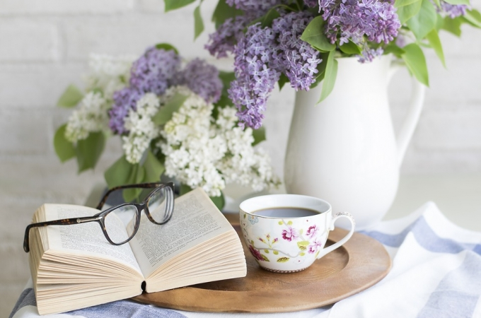 Open book sits on a tray next to a mug of cocoa and a vase of lilac flowers