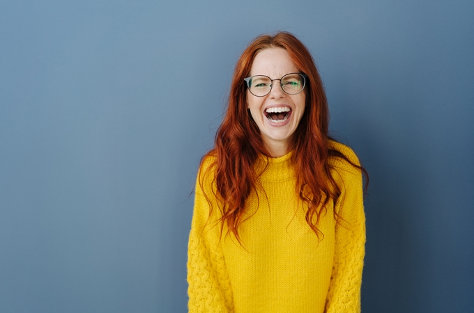 Young redheaded woman laughing at the camera over a blue studio background