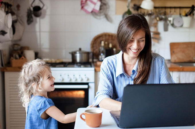 Working mother typing on laptop and laughing with daughter