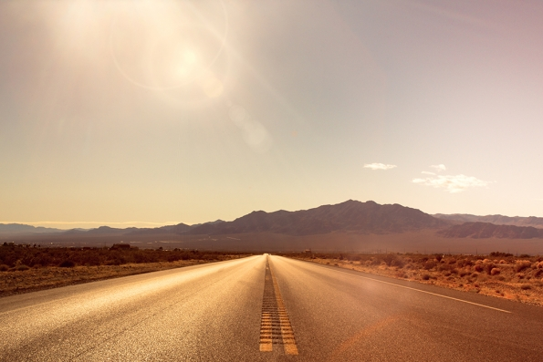 Road through a desert with mountains and sunlight in the distance