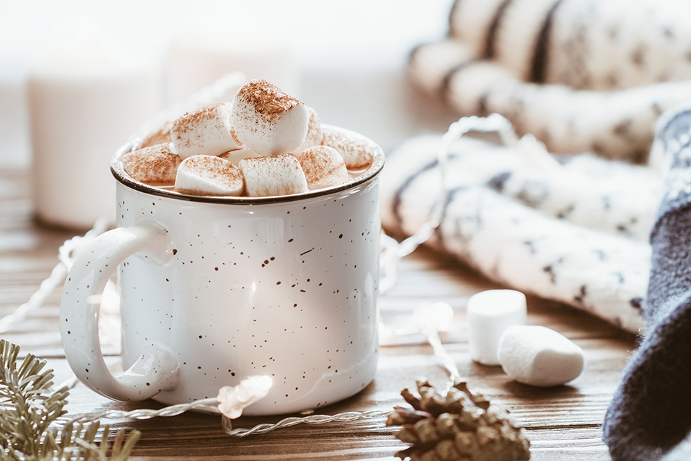 Hot cocoa with marshmallow in a white ceramic mug surrounded by winter things on a wooden table