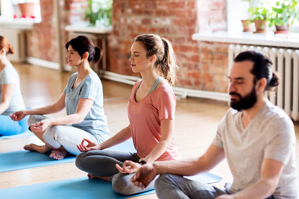 Group of people meditating in lotus pose at yoga studio
