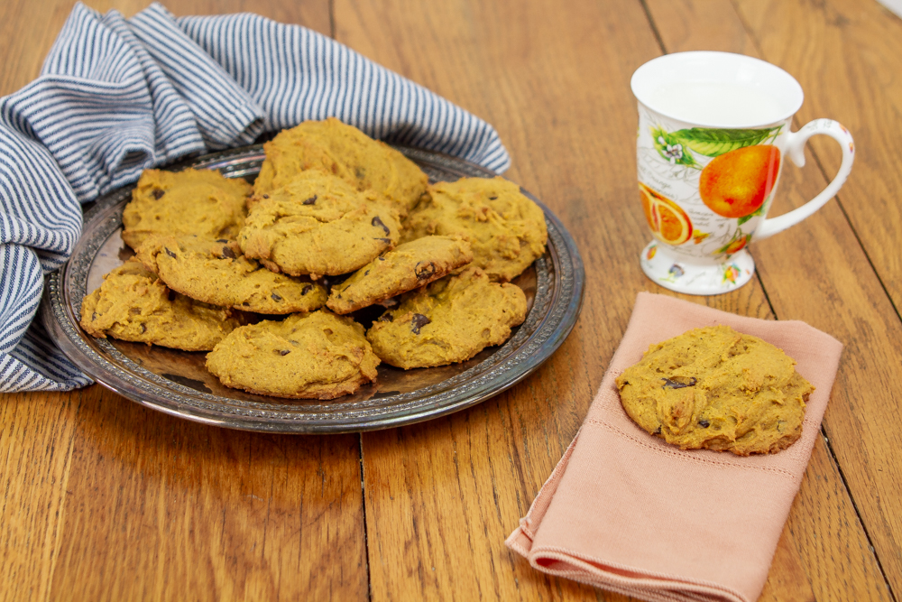 Pumpkin Chocolate Chip Cookies on a plate and napkin with a mug full of milk
