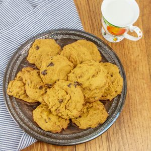 A plate of pumpkin chocolate chip cookies next to a glass of milk