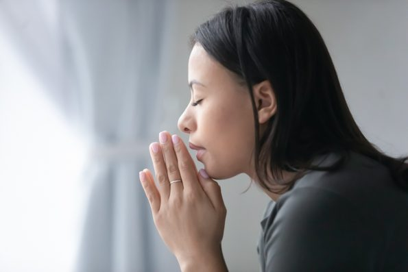 Woman praying to God at home