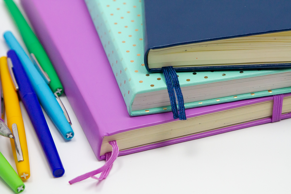 Stack of journals next to several colorful markers