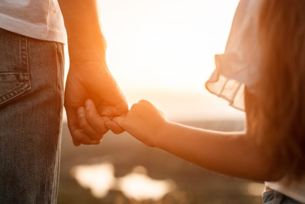 Man and girl holding pinkies while standing in field at sunset